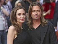 Angelina Jolie poses with her husband Brad Pitt as they arrive for the world premiere of his film World War Z in London June 2, 2013. REUTERS/Neil Hall
