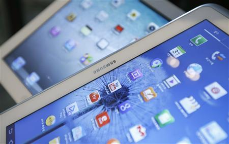 Samsung Electronics' Galaxy Tab (front) and Apple's iPad are seen in this picture illustration taken in Seoul May 13, 2013. REUTERS/Kim Hong-Ji