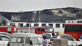 Машина спасателей и пожарных у горящей птицебойни в Дэхуэе 3 июня 2013 года. По меньшей мере 113 человек стали жертвами пожара на птицебойне на северо-востоке Китая, сообщили местные власти и СМИ. REUTERS/Xinhua/Wang Haofei