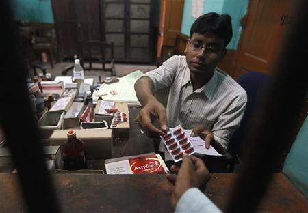 A pharmacist gives free medicine provided by the government, to a patient inside a government hospital in Kolkata July 3, 2012. REUTERS/Rupak De Chowdhuri/Files