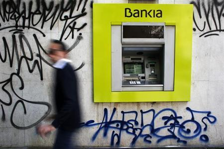 A man walks past a Bankia bank branch with graffitti on it in Madrid May 28, 2013. REUTERS/Susana Vera