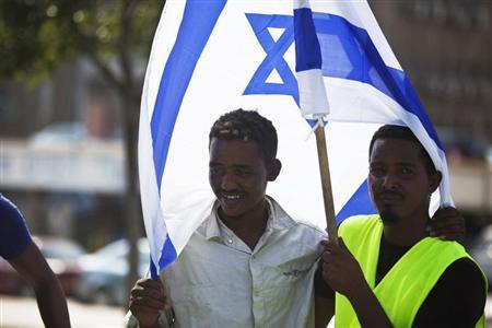 African migrants from Eritrea hold an Israeli flag during a protest near the Ministry of Defence in Tel Aviv October 18, 2012. REUTERS/Nir Elias