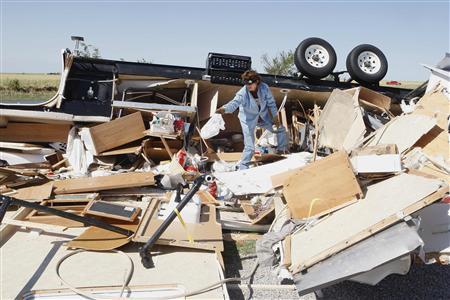 Mikie Hooper of Tuttle, Oklahoma, collects her belongings from her RV which was destroyed by a tornado in El Reno, Oklahoma, June 1, 2013. REUTERS/Bill Waugh