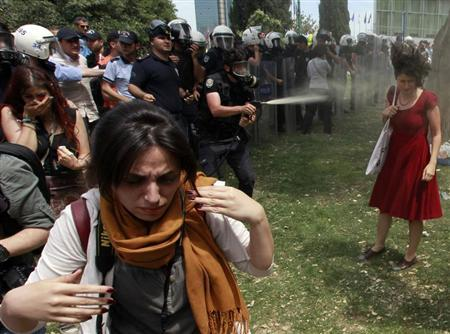 A Turkish riot policeman uses tear gas as people protest against the destruction of trees in a park brought about by a pedestrian project, in Taksim Square in central Istanbul May 28, 2013. REUTERS/Osman Orsal