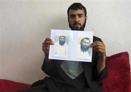Shahedullah, 24, holds pictures of his brother Mohammad Qasim, whose body according to Shahedullah was found close to the COP Nerkh military base, in Wardak province May 26, 2013. REUTERS/Stringer
