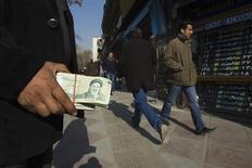 Меняла держит пачку с иранскими реалами на торговой улице в Тегеране 7 января 2012 года. Соединенные Штаты в понедельник усилили давление на Иран за разработку ядерной программы, введя санкции, нацеленные на ослабление национальной валюты и затрагивающие автоиндустрию исламской республики. REUTERS/Raheb Homavandi