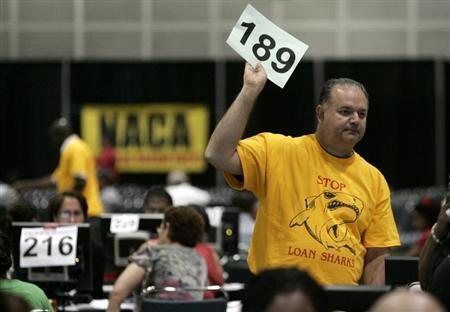 A NACA loan counselor holds up a sign to call a home owner to his desk at the ''Save the Dream'' home loan modification event, coordinated by the non-profit advocacy group Neighborhood Assistance Corporation of America (NACA), at the Los Angeles Convention Center in Los Angeles, California September 25, 2009. REUTERS/Danny Moloshok