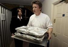 Celebrity chef Jamie Oliver (C) carries out food for a G20 leaders dinner at Downing Street in London April 1, 2009 file photo. REUTERS/Christopher