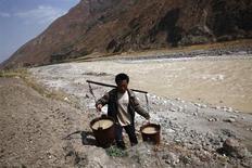 La contaminación en las zonas rurales de China empeoró en 2012 como resultado de la intrusión de la industria y la minería en suelo agrario, además de por aumento de la ganadería y el mayor uso de suelo para su explotación, dijo el martes el Ministerio de Medio Ambiente. En la imagen, un hombre llena unos cubos de agua de un arroyo contaminado usado para el consumo, en el distrito de Kunming, en la provincia de Yunnan, el 20 de marzo de 2013. REUTERS/Stringer