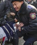 Полицейские задерживают участника акции протеста в Алма-Ате 25 февраля 2012 года. Полиция Алма-Аты во вторник задержала активиста немногочисленного объединения мусульман, который добивался встречи с мэром в надежде обсудить социальные проблемы самого населенного города крупнейшей экономики Центральной Азии. REUTERS/Shamil Zhumatov