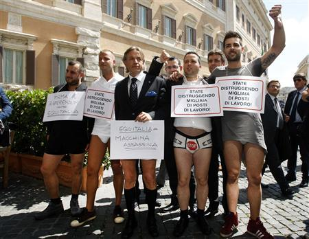 Italian businessmen pose for photographers in their shirts and underwear while carrying signs that read ''You are killing thousands of jobs,'' during a protest demanding the abolition of tax collection agency Equitalia, outside the parliament in Rome June 4, 2013. EUTERS/Remo Casilli