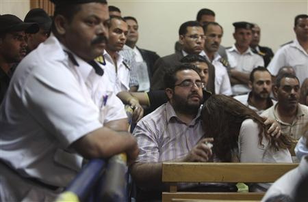 Friends of Egyptian suspects react as they listen to the judge's verdict at a court room during a case against foreign non-governmental organisations (NGOs) in Cairo June 4, 2013. REUTERS/Asmaa Waguih