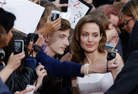 Angelina Jolie (C) poses for a picture with a fan during the premiere of the film World War Z in Berlin June 4, 2013. REUTERS/Tobias Schwarz