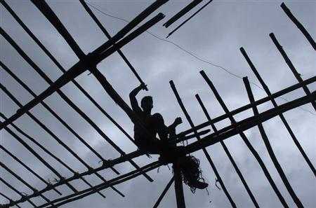 A man is silhouetted against the sky while sitting on wooden scaffolding, as he constructs a temporary tent in Mumbai August 6, 2012. REUTERS/Danish Siddiqui/Files