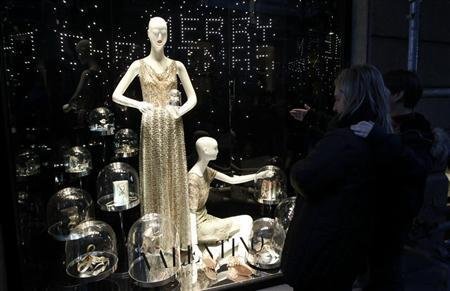 Shoppers look at luxury goods displayed in a window in downtown Milan December 8, 2011. REUTERS/Stefano Rellandini