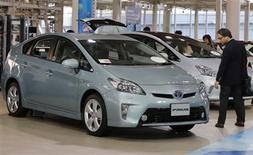 Мужчина смотрит на автомобиль Toyota Prius в шоу-руме компании в Токио 14 ноября 2012 года. Toyota Motor Corp отзывает около 242.000 гибридов по всему миру, включая суперпопулярную модель Prius, из-за дефекта в конструкции тормозов, заявил в среду автопроизводитель. REUTERS/Yuriko Nakao