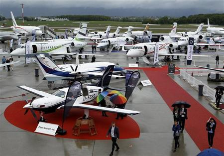 Visitors walk past aircrafts in the static display area during the Annual European Business Aviation Convention & Exhibition (EBACE) at Cointrin airport in Geneva May 21, 2013. REUTERS/Denis Balibouse