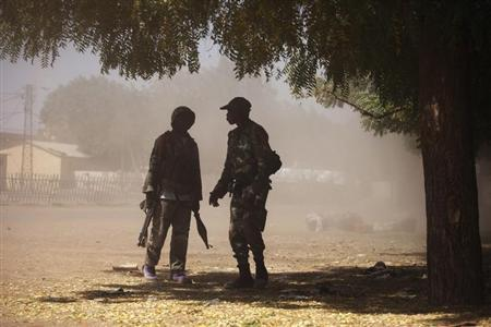 Malian soldiers talk to each other in a cloud of dust during fighting with Islamists in Gao February 21, 2013. REUTERS/Joe Penney
