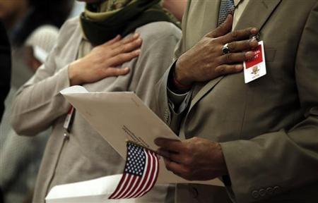 Immigrants put their hands to their hearts as the national anthem is played during a special naturalization ceremony at the Department of Justice in Washington May 28, 2013. REUTERS/Kevin Lamarque