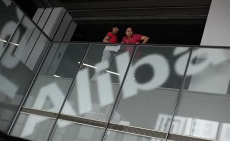 Employees stand next to a logo of Alibaba (China) Technology Co. Ltd during a media tour organized by government officials at its headquarters on the outskirts of Hangzhou, Zhejiang province June 20, 2012. REUTERS/Carlos Barria