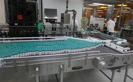 Employees of Teva Pharmaceutical Industries work near pill bottles on a conveyor belt at the company's Jerusalem oral solid dosage plant (OSD) December 21, 2011. REUTERS/Ronen Zvulun
