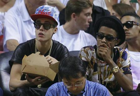 Pop singer Justin Bieber (L) watches the Miami Heat play against the Indiana Pacers in Game 7 of their NBA Eastern Conference final basketball playoff in Miami, Florida June 3, 2013. REUTERS/Joe Skipper