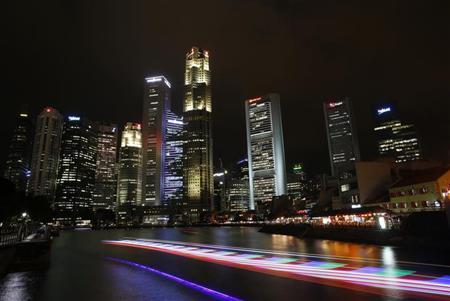 Bumboats cruise past bars and restaurants in Boat Quay (R), situated near skyscrapers in the central business district of Singapore March 19, 2013. REUTERS/Edgar Su