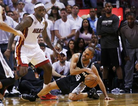 San Antonio Spurs' Tony Parker slips while being guarded by Miami Heat's LeBron James (L) during the fourth quarter in Game 1 of their NBA Finals basketball playoff in Miami, Florida June 6, 2013. REUTERS/Mike Segar