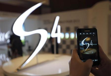 A man takes a photograph of a logo of Samsung Electronics Co Ltd's latest flagship smartphone S4 during its launch event at the company's headquarters in Seoul April 25, 2013. REUTERS/Kim Hong-Ji