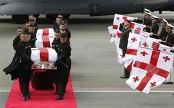 Солдаты почетного караула несут гробы с телами погибших в Афганистане грузинских солдат в аэропорту Тбилиси 16 мая 2013 года. Семь грузинских солдат погибли в четверг в Афганистане в результате взрыва смертника, управлявшего грузовиком со взрывчаткой, сообщили представители НАТО и Грузии. REUTERS/David Mdzinarishvili
