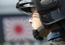 Японский спецназовец следит за акцией протеста возле российского посольства в Токио в День северных территорий, 7 февраля 2013 года. Правительство Японии одобрило законопроект об учреждении совета национальной безопасности с целью усиления влияния премьер-министра на внешнюю политику на фоне угроз со стороны Северной Кореи и территориального спора с Китаем. REUTERS/Yuya Shino