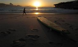 A man walks near a surfboard on Copacabana beach, where Pope Francis is expected to lead a mass during his upcoming visit, in Rio de Janeiro May 9, 2013. REUTERS/Sergio Moraes