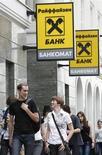 Люди проходят мимо отделения банка Райффайзен в Москве 19 мая 2013 года. Новый глава Raiffeisen Bank International (RBI) Карл Севельда, пришедший на смену Герберту Степичу, сказал, что банк по-прежнему видит основным плацдармом для бизнеса Центральную и Восточную Европу и не собирается уходить из России и Венгрии. REUTERS/Sergei Karpukhin