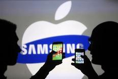 Homens posam com um Samsung Galaxy S3 (E) e um iPhone 4 (D) nesta foto ilustrativa em Zenica, na Bósnia-Herzegovina. A Samsung perdeu 12 bilhões de dólares em valor de mercado na sexta-feira, atingida por rebaixamentos de recomendações por corretoras, que ressaltaram preocupações com a desaceleração das vendas de seu principal produto, o smartphone Galaxy S4. 17/05/2013 REUTERS/Dado Ruvic