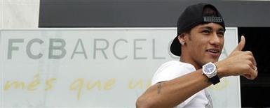Jogador brasileiro Neymar acena aos fotógrafos em frente aos escritórios do Barcelona próximos ao estádio Camp Nou, em Barcelona. O cantor espanhol e torcedor do Real Madrid Julio Iglesias emprestou seu avião particular a Neymar para que o jogador pudesse viajar a Barcelona para a apresentação no time catalão esta semana, informou a imprensa local. 3/06/2013. REUTERS/Albert Gea