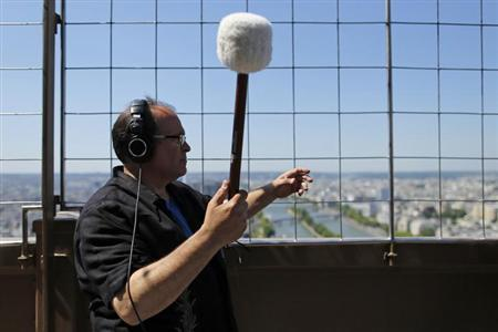 U.S. composer Joseph Bertolozzi makes sounds by striking the surface of the Eiffel Tower for a musical project called 'Tower music' in Paris June 7, 2013. REUTERS/Benoit Tessier