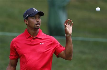 Tiger Woods of the U.S. catches his ball before making a par on the 11th hole during the final round of the Memorial Tournament at Muirfield Village Golf Club in Dublin, Ohio June 2, 2013. REUTERS/Matt Sullivan