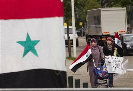 Two female members of the Syrian community in The Netherlands carry their national flag as they arrive to demonstrate in front of the International Criminal Court (ICC) offices in The Hague June 7, 2011. REUTERS/Michael Kooren