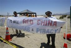 Protestors adjust signs as they demonstrate on an empty lot blocks from where Chinese President Xi Jinping will meet U.S. President Barack Obama in Rancho Mirage, California June 7, 2013. REUTERS/Sam Mircovich