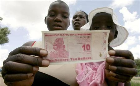 A woman displays a new Z$10 banknote in Harare, February 4, 2009. Zimbabwe's central bank revalued its dollar again on Monday, lopping another 12 zeros off its currency to try to tame hyperinflation and avert total economic collapse. REUTERS/Philimon Bulawayo