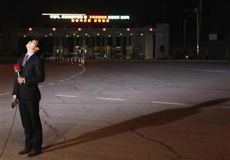 A local TV reporter reacts as he prepares for a news report in front of an empty gate at the customs, immigration and quarantine (CIQ) office, just south of the demilitarized zone separating North Korea from South Korea in Paju, north of Seoul April 29, 2013. REUTERS/Lee Jae-Won