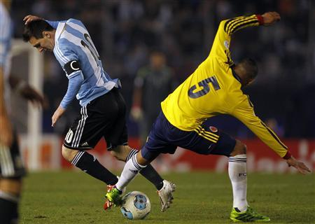 Lionel Messi (L) of Argentina tries to dribbles the ball under pressure from Aldo Ramirez of Colombia during their 2014 World Cup qualifying soccer match in Buenos Aires, June 7, 2013. REUTERS/Marcos Brindicci