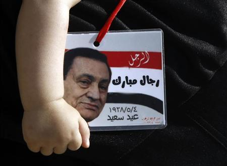 A boy holds a card with a picture of Egypt's former president Hosni Mubarak outside the police academy where Mubarak's trial will take place, in Cairo May 11, 2013. REUTERS/Amr Abdallah Dalsh
