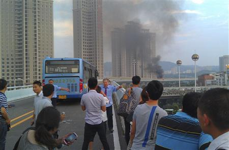 People are held back from the site of a bus fire in Xiamen, Fujian province June 7, 2013. REUTERS/Stringer