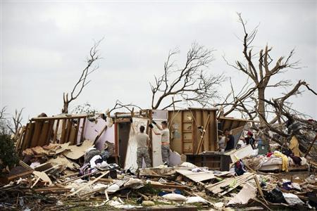Members of the National Guard help a homeowner look for items to salvage several days after the building had been destroyed by a tornado in Moore, Oklahoma, May 24, 2013. REUTERS/Lucas Jackson