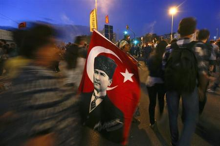 A woman sells Turkish flags, with an image of the founder of modern Turkey Mustafa Kemal Ataturk depicted on them, as anti-government protesters gather in Istanbul's Taksim square June 7, 2013. REUTERS/Yannis Behrakis