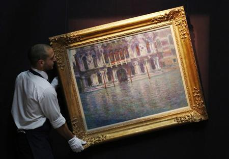 A Sotheby's employee poses with Claude Monet's artwork ''Le Palais Contarini'' at Sotheby's auction house in London June 7, 2013. REUTERS/Luke MacGregor