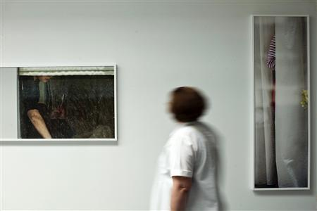 A woman attends a photo exhibition called 'The Neighbors' by fine art photographer Arne Svenson at Julie Saul Gallery in New York in this June 1, 2013 file photo. Svenson, who secretly used a zoom lens to photograph his neighbors napping and eating has caused a citywide stir -- and two legal actions so far. REUTERS/Eduardo Munoz/Files