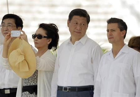 China's first lady Peng Liyuan (2nd L) takes a photograph as China's President Xi Jinping (2nd R) talks with his Mexican counterpart Enrique Pena Nieto during a visit at the archaeological site of Chichen Itza in the peninsula of Yucatan June 6, 2013. REUTERS/Victor Ruiz Garcia