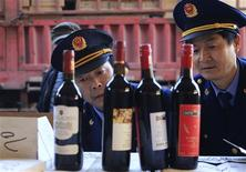 Police officers check bottles of confiscated fake wines before destroying them in Xi'an, Shaanxi province January 4, 2012. REUTERS/Stringer